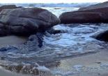 A wave through rocks on the beach